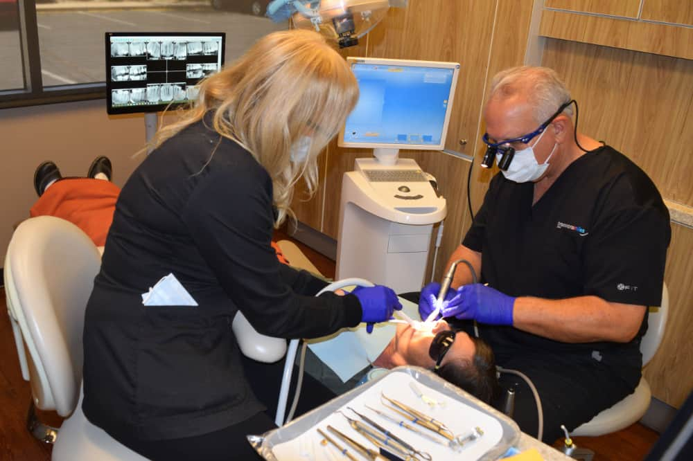 Dr. Brannon performing a root canal on patient with help from Dental Assistant Terry K
